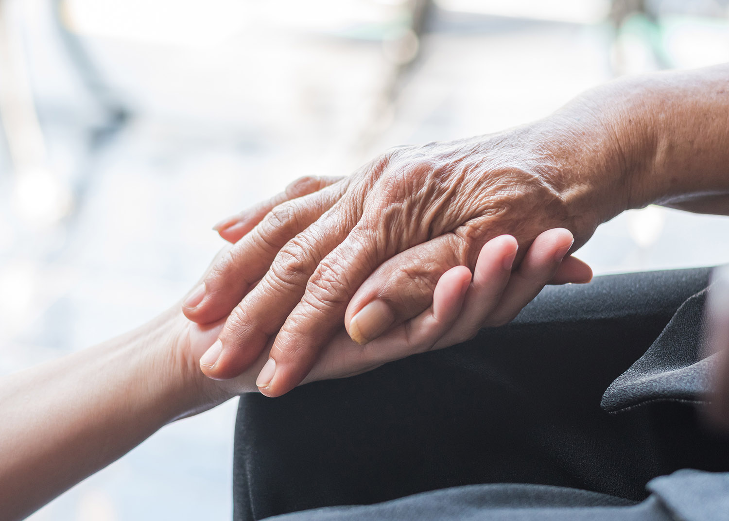 Elder holding younger person's hand